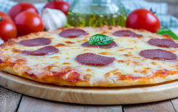 Homemade pepperoni pizza on a wooden board Stock Images