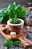 Homemade pesto made of organic basil on the board of olives with parmesan and garlic Royalty Free Stock Photos