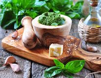 Homemade pesto made of organic basil on the board of olives with parmesan and garlic Stock Photography