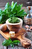 Homemade pesto made of organic basil on the board of olives with parmesan and garlic Royalty Free Stock Photography
