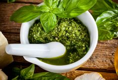 Homemade pesto sauce with basil and pine nuts in white mortar Royalty Free Stock Photos
