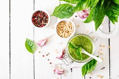 Homemade pesto sauce fresh basil, pine nuts and garlic. On white wooden background. Italian food. Top view. Flat lay Royalty Free Stock Photo
