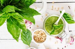 Homemade pesto sauce fresh basil, pine nuts and garlic. On white wooden background. Italian food. Top view. Flat lay Royalty Free Stock Photography