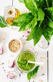Homemade pesto sauce fresh basil, pine nuts and garlic. On white wooden background. Italian food. Top view. Flat lay Stock Images