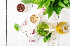 Homemade pesto sauce fresh basil, pine nuts and garlic. On white wooden background. Italian food. Top view. Flat lay Stock Photo