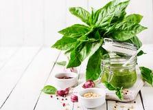 Homemade pesto sauce fresh basil, pine nuts and garlic. On white wooden background. Italian food Royalty Free Stock Photos