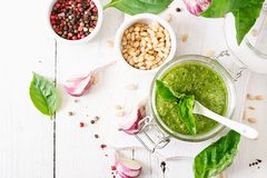 Homemade pesto sauce fresh basil, pine nuts and garlic. On white wooden background. Italian food. Top view. Flat lay Royalty Free Stock Image