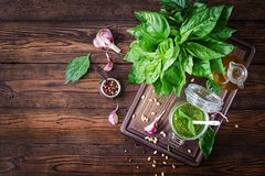 Homemade pesto sauce fresh basil, pine nuts and garlic. On wooden background. Italian food. Top view. Flat lay Stock Image
