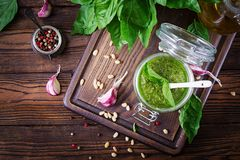 Homemade pesto sauce fresh basil, pine nuts and garlic. On wooden background. Italian food. Top view. Flat lay Stock Images