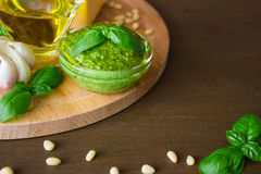 Homemade pesto sauce with ingredients over old table. Front view. with a copypaste space Royalty Free Stock Photo