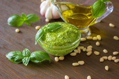 Homemade pesto sauce with ingredients over wooden table. Front view Stock Photos