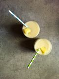 Homemade piña colada in two glasses with striped paper straws Royalty Free Stock Photos