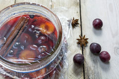 Homemade pickled plums  in a glass jar on rustic wood Stock Images
