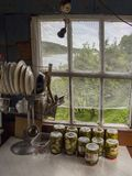 Homemade pickles in villagers house. Villagers house inside view of homemade pickles on the table and a beautiful landscape view outside the window. For the best stock photos