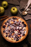 Homemade pie with apples and blackberry on dark stone background. Stock Photos