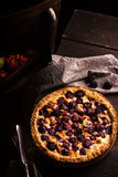 Homemade pie with apples and blackberry on wooden dark table. Royalty Free Stock Image