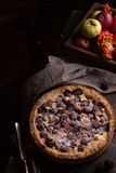 Homemade pie with apples and blackberry on wooden dark table. Royalty Free Stock Images