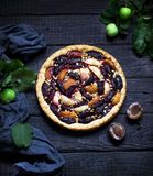 Homemade pie with plums and apples on dark wooden background. royalty free stock image