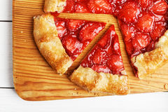 Homemade pie with strawberries on white wooden table