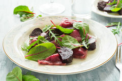 Homemade pink ravioli tortellini with goat cheese decorated beet leaves, beetroot slices and cranberry Royalty Free Stock Photo