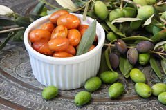 Homemade piquant olives, olive tree branch and raw olives. Royalty Free Stock Photography