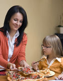 Homemade pizza. A woman and young girl eating homemade pizza together at home royalty free stock photos