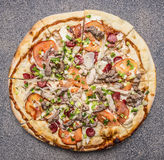 Homemade pizza with bacon, tomatoes and cheese on rustic background top view close up Stock Image
