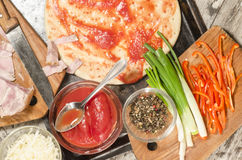 Homemade pizza on baking tray and Ingredients for cooking Stock Photography