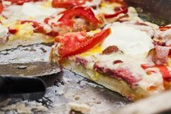 Homemade pizza. On a baking tray. Sliced with a pizza cutter (knife). On a wooden board Royalty Free Stock Photos