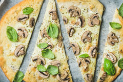 Homemade pizza with basil cut in slices on baking paper Stock Photos
