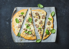 Homemade pizza with basil cut in slices on baking paper Stock Image