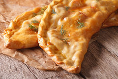 Homemade pizza calzone macro on a paper on the table. horizontal Royalty Free Stock Photography