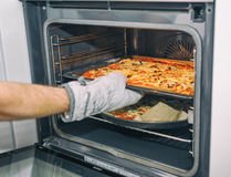 Homemade pizza coming out of oven. Healthy food concept. Selective focus. Stock Photos