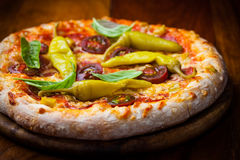 Homemade pizza with dried tomatoes and hot peppers stock images