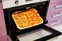 Homemade pizza in electric oven in the kitchen Stock Photography