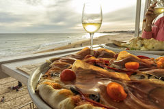 Homemade pizza with ham tomato olives and peppers with glass of Royalty Free Stock Photo