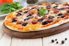 Homemade pizza with hunter sausages, bacon, olives and basil Royalty Free Stock Photo