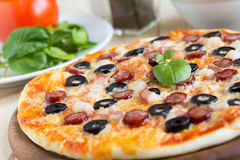 Homemade pizza with hunter sausages, bacon, olives and basil Stock Photo
