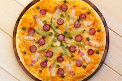 Homemade pizza with hunter sausages, bacon, peas and pickled cuc Royalty Free Stock Photography