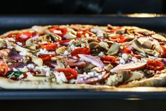 Homemade pizza with mushrooms, ham and mozzarella, prepared for. Baking in the oven Royalty Free Stock Image