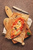 Homemade pizza with mushrooms, tomato and cheese on a cutting board, brown stone background. Top view, flat lay royalty free stock photography