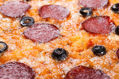 Homemade pizza with salami, parmesan cheese,  background closeup Royalty Free Stock Photo