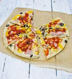 Homemade pizza. Sliced homemade pizza on baking paper, on a wooden table royalty free stock image