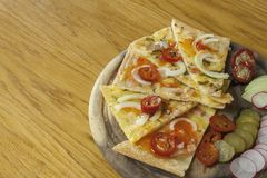 Homemade pizza, sliced on a wooden chopping boards, flavored with chilli peppers. Royalty Free Stock Photos