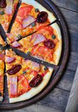Homemade pizza with smoked meat, dried and fresh tomatoes, capers, onions and tomato sauce Royalty Free Stock Photography