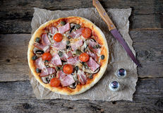 Homemade pizza with smoked meat, ham, mushrooms, cherry tomato, capers and cheese. Stock Images