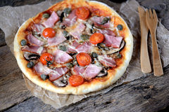 Homemade pizza with smoked meat, ham, mushrooms, cherry tomato, capers and cheese. Royalty Free Stock Photos