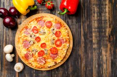Homemade pizza with tomatoes and mushrooms on a wooden table with vegetables stock photo