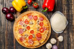 Homemade pizza with tomatoes and mushrooms on a wooden table with vegetables stock photos