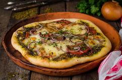 Homemade pizza with zaatar, tomatoes, onion and cheese on wooden background. Eastern cuisine. Selective focus Stock Images